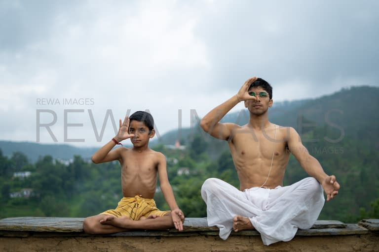 Handsome boy doing yoga with a kid